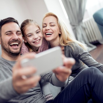 Happy family taking selfie on couch at home in the living room.
