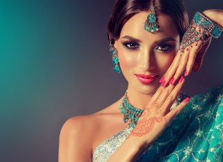 Portrait smiling of beautiful indian girl. Young indian woman model with blue kundan jewelry set . Traditional Indian costume .