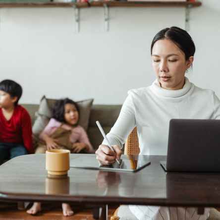 mum working on laptop at table with bored children behind