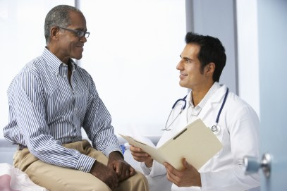 older man talking to his doctor and smiling