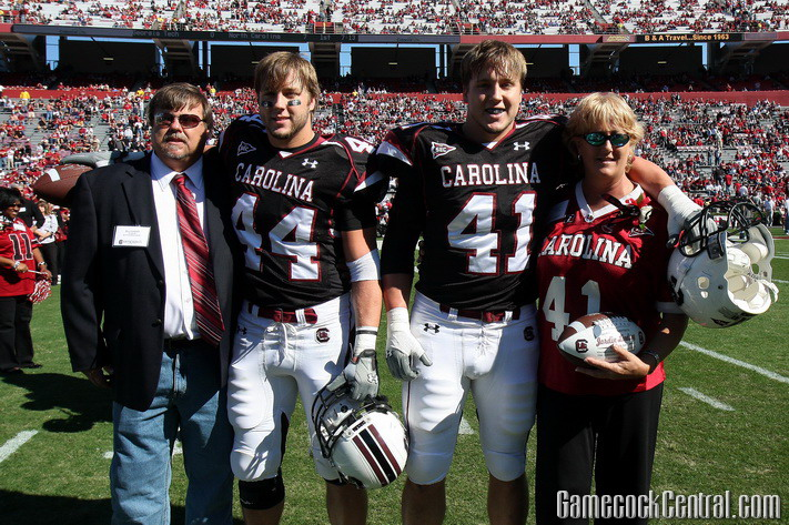 Dusty (44) and Jordy Lindsey (41) share a moment with their parents at South Carolina Senior Day last Saturday. The twins have been bashing heads alongside each other since their days playing football for the Mobile, Ala., Mims Park Redskins, where their Dad was a coach.