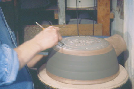 Fig. 12: Colored liquid clay is brushed onto the shell to begin the decorating process.