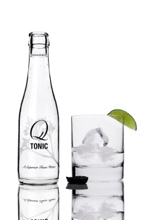 Q Tonic bottle with rocks glass partially filled with ice and a small amount of gin. A lime wedge is on the rim of the glass and the black Q Tonic bottle cap is off the bottle, upside down, next to the rocks glass.
