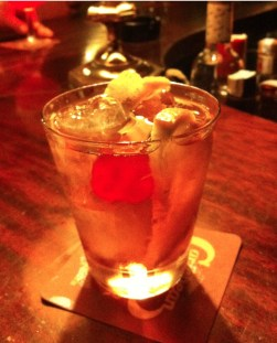 An Old Fashioned sits on fine-grained wood bar