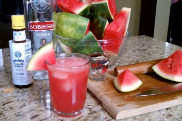 Fresh cut watermelon, a bottle vodka, and a bottle of bitters behind a glass