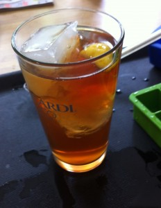 iced tea with large ice cubes and a slice of lemon in clear pint glass