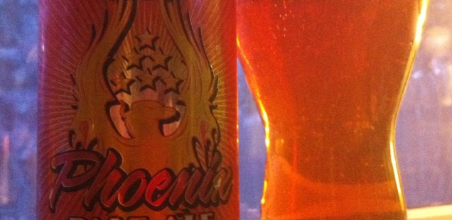 A can of SlyFox Phoenix Pale Ale and the beer poured into a pint glass. The beer is dark amber in color.