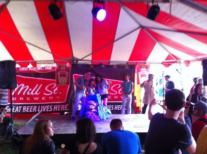 Two people pose next to a woman dressed as a blue mermaid under the Mill St. Brewery tent at Toronto's Festival of Beer