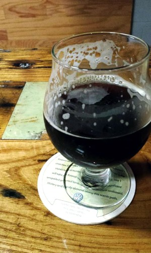 A tulip glass with a dark beer from Destination Unknown