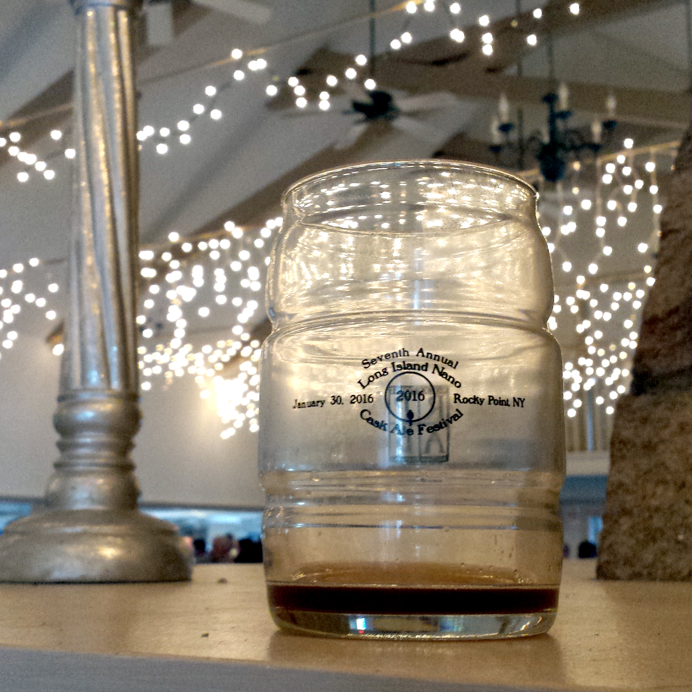 A cask shaped glass from the 2016 Long Island Nano Cask Ale Festival with a small amount of dark beer lingering in the glass