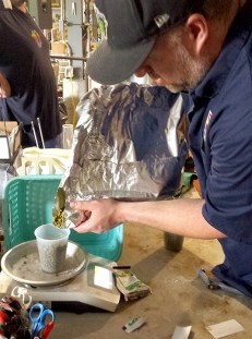 Chris Kelley measuring hops for his beer Go Bigg or Go Home