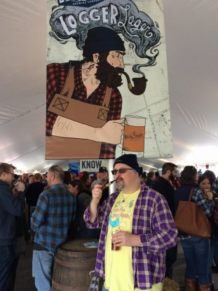 Fervere stands by the sign welcoming people to the 2016 Blue Point Logger Lager