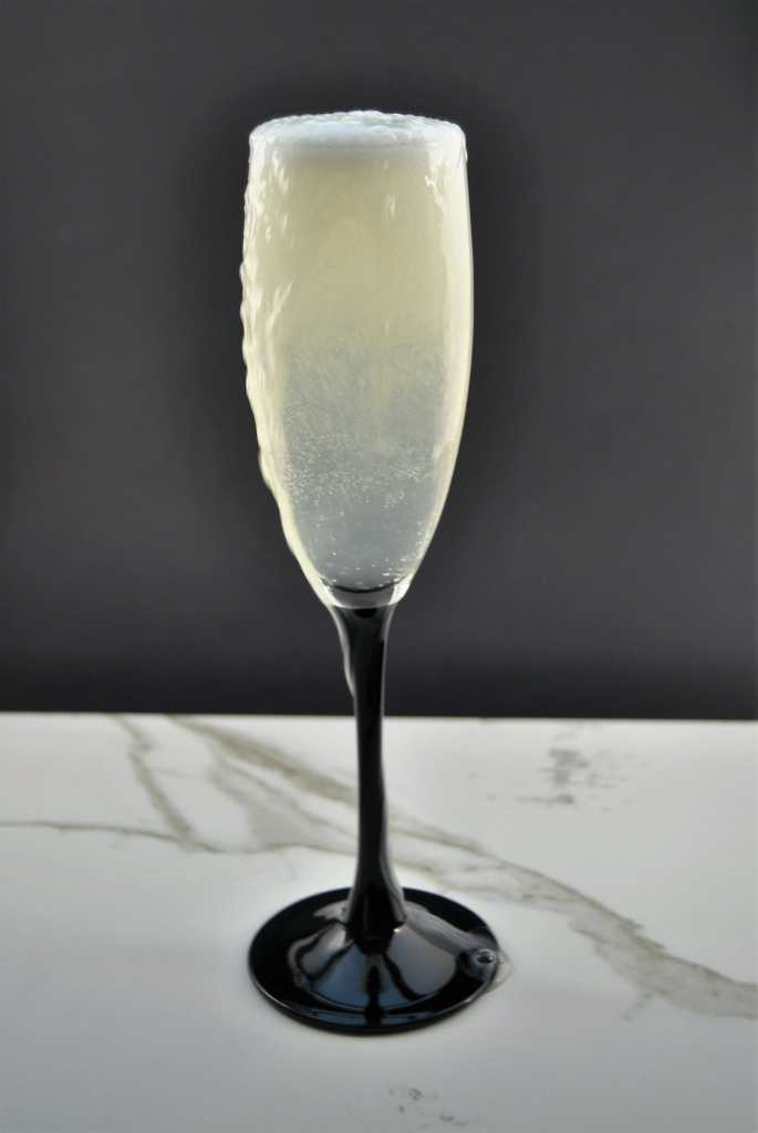 Champagne glass with bubbles on top on marble