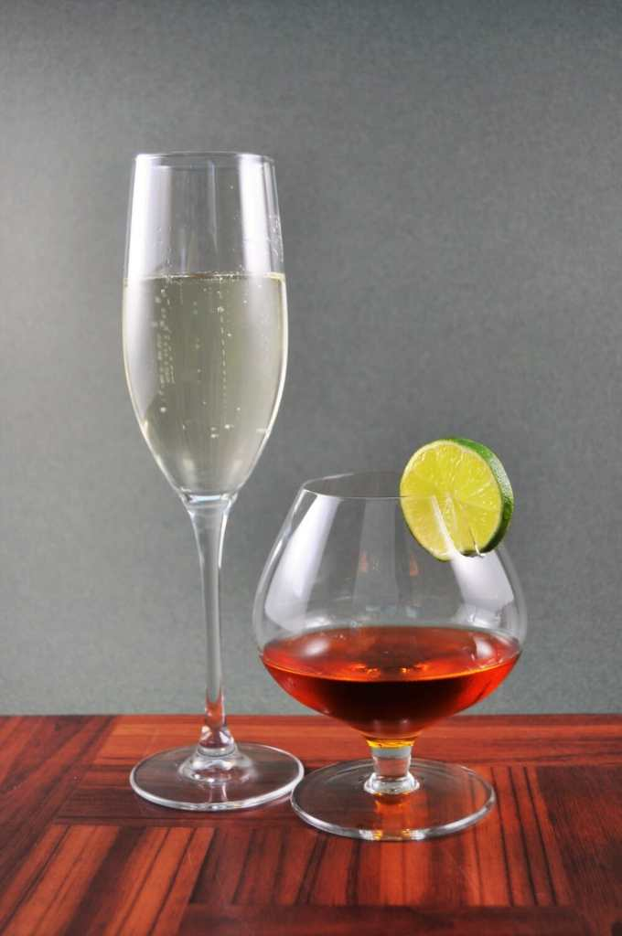 One champagne flute filled with champagne and one small cocktail glass filled with amber liquid and topped with a lime