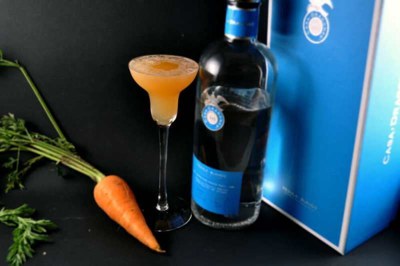 Cocktail next to Tequila bottle and carrot