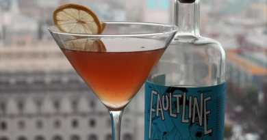 Orange cocktail next to gin bottle with blue label with buildings behind
