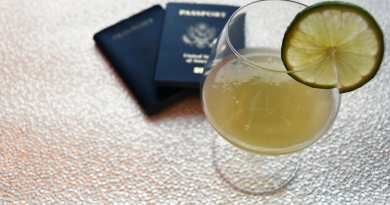 Cocktail with lime wheel garnish in front of 2 passports