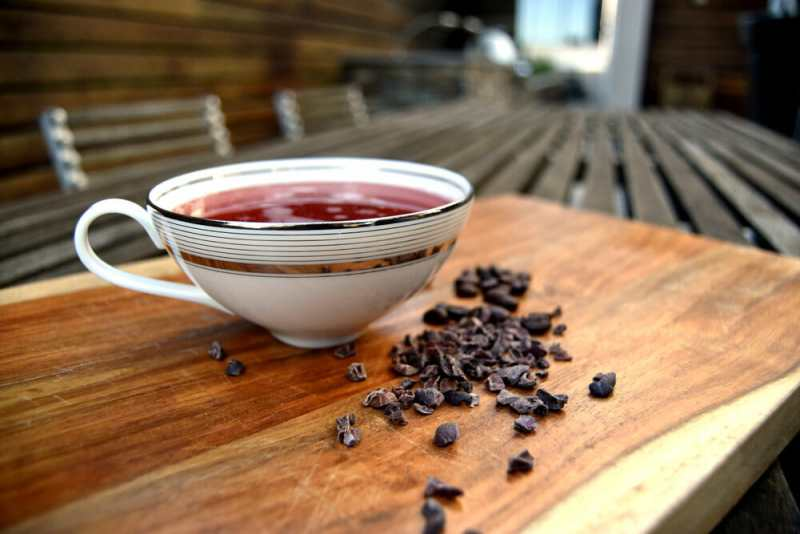 Tea mug filled with reddish liquid with coffee beans in front of it on top of cutting board