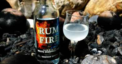 Cocktail next to bottle of Rum Fire on top of rocks in a fire pit