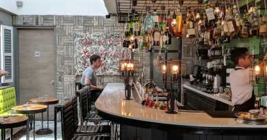 Bright bar with several bottles hanging from an open cieling
