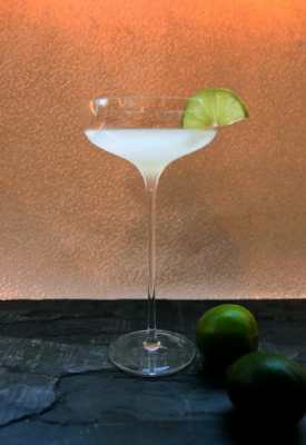 Cocktail in a long stemmed glass with a lime garnish