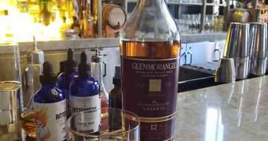 Whisky glass next to bottle on busy bar with lighting behind