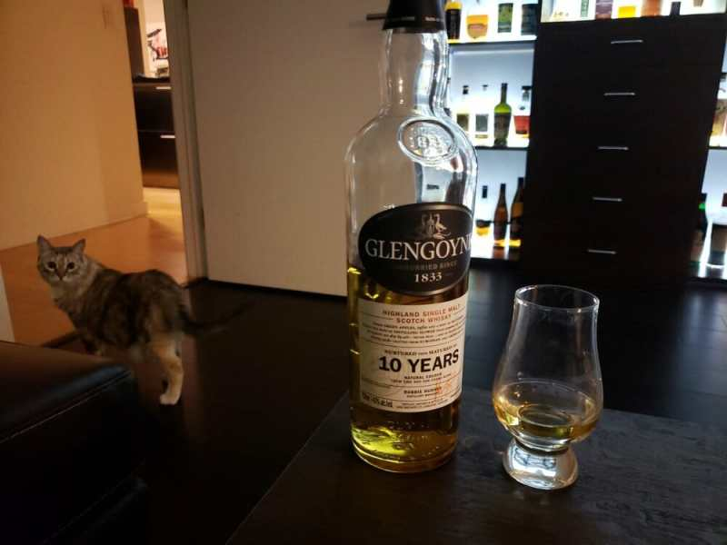 Whisky bottle next to whisky glass with cat in background