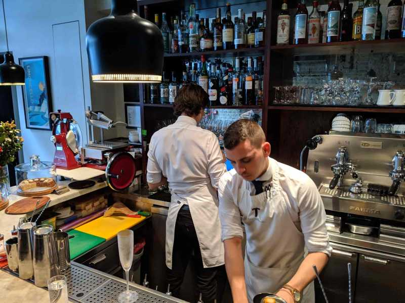Two bartenders facing in opposite directions in front of a small darkly lit bar with an overhead light
