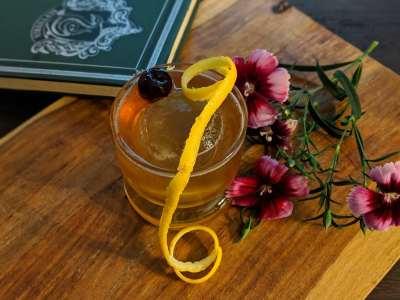 Cocktail with lemon twist and flower garnish