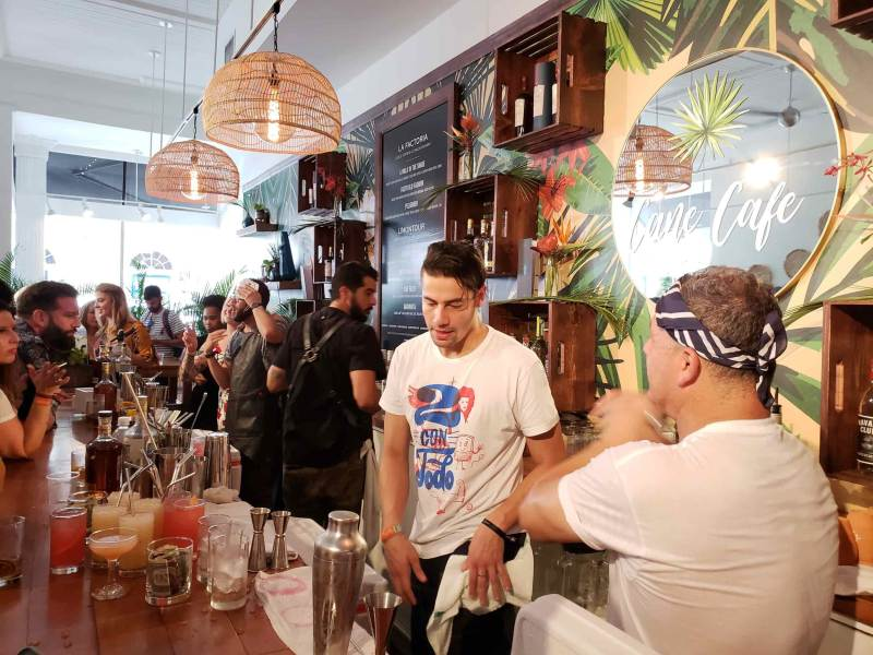 Busy bar with several bartenders making drinks