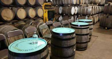 Four barrels with blue tops in front of more barrels