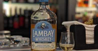 Bottle of Irish whiskey next to tasting glass.