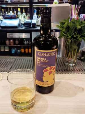 Bottle of Samaroli rum next to glass of rum