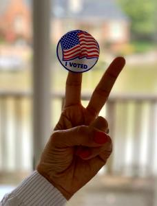 Woman with an I voted sticker in her fingers with the victory sign. A citizen duty & civil right.
