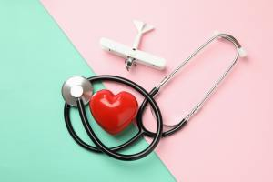 Stethoscope, heart and plane on two tone background