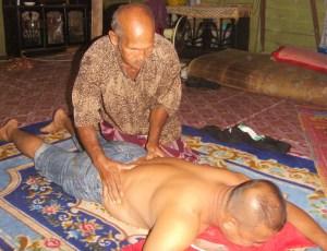 Pak Su sedang mengurut seorang penduduk kampung yang datang mengurut di rumahnya di Kampung Kederang, Setiu.