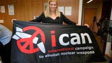 La directrice de l'ICAN, Beatrice Fihn, tient une banderole de l'organisation, après avoir obtenu le prix Nobel de la paix, le 6 octobre 2017 à Genève