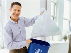 portrait of a mid adult man holding a garbage bin and a garbage bag