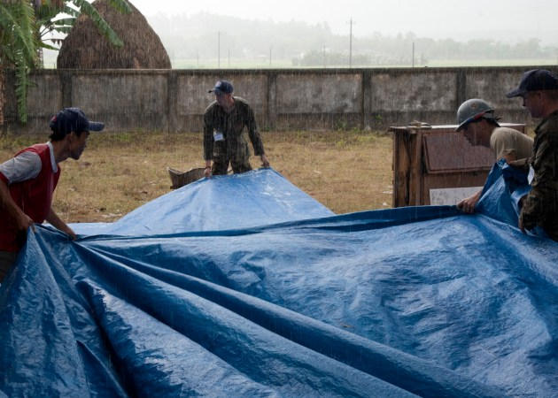 U.S. service members and a Vietnam People's Army member protect a concrete pad from the rain at Binh Thanh Dong primary school, Quang Ngai province, Vietnam, during an engineering project, March 25, 2015. Operation Pacific Angel 15-3 is a multilateral humanitarian assistance civil military operation, which improves military-to-military partnerships in the Pacific while also providing medical health outreach, civic engineering projects and subject matter exchanges among partner forces. (U.S. Air Force photo by Staff Sgt. Tong Duong/ Released)