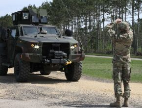 A soldier standing in front of an Army truck