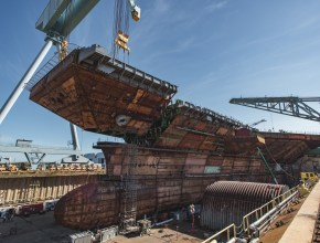 a ship being built in dry dock using a crane