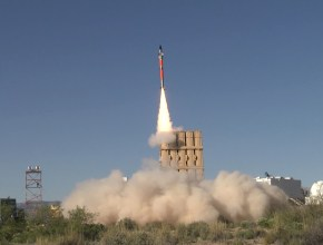 missile launch with visible exhaust creates a cloud of dust