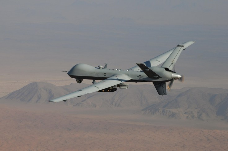 military drone flying over the desert