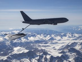 a bomber aircraft is refueled midair above snow-capped mountains