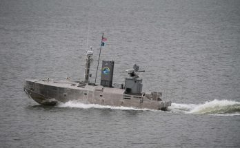 small unmanned vessel outfitted with electronics and weaponsmoves through the water