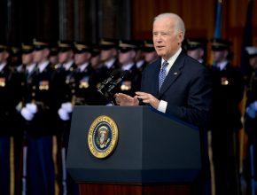Vice President Joe Biden standing behind a podium in front of uniformed soldiers