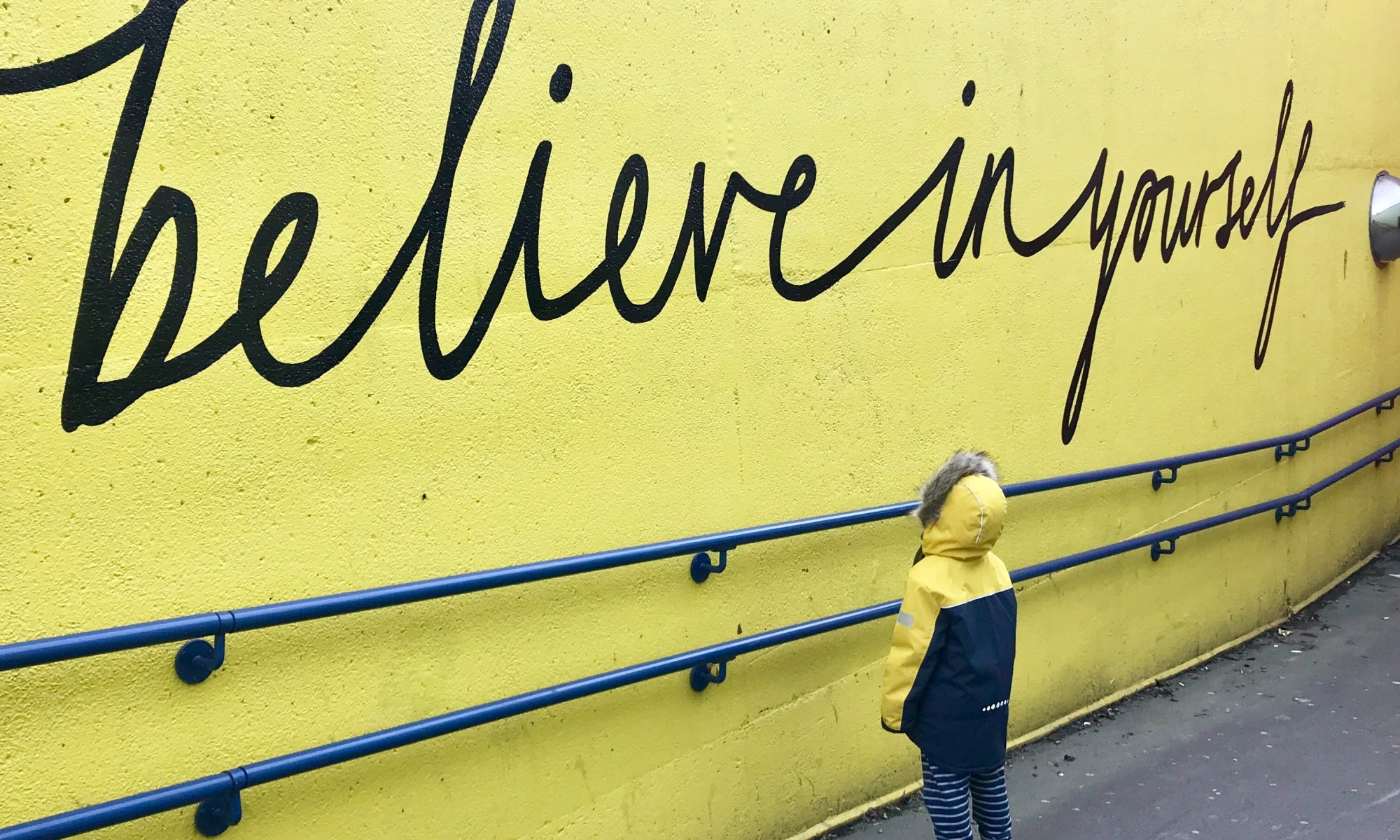 """A boy looking at a yellow wall that says """"believe in yourself"""""""