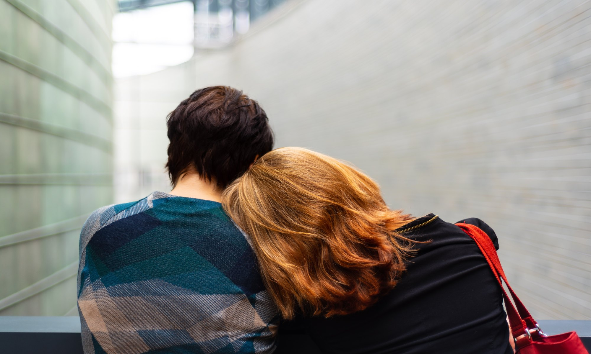 A female leaning her head against a man's shoulder