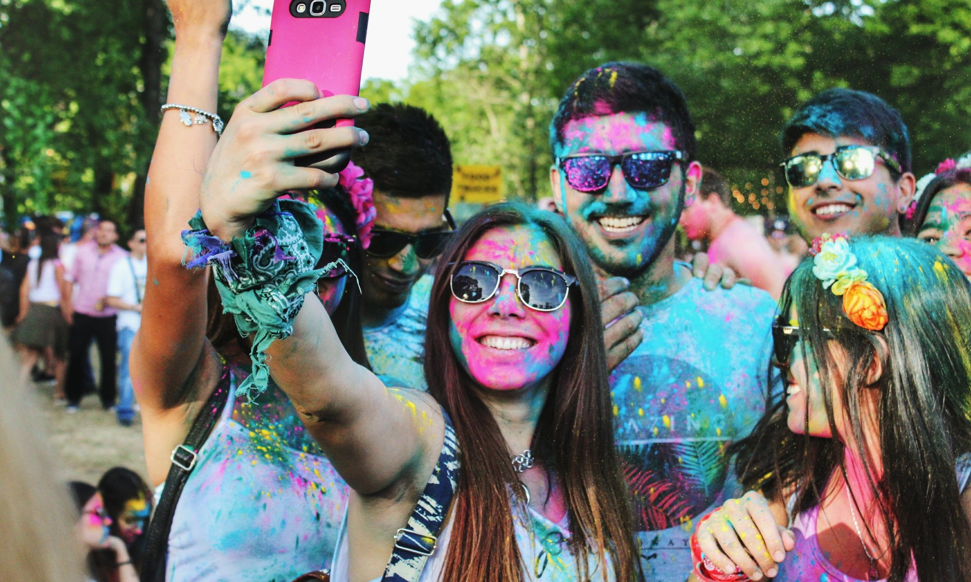 Millennials sprayed in skin paint taking a group picture with a cell phone