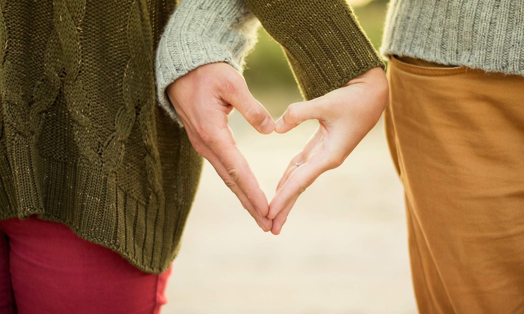 Two people being tender-hearted and forming a heart shape with their hands